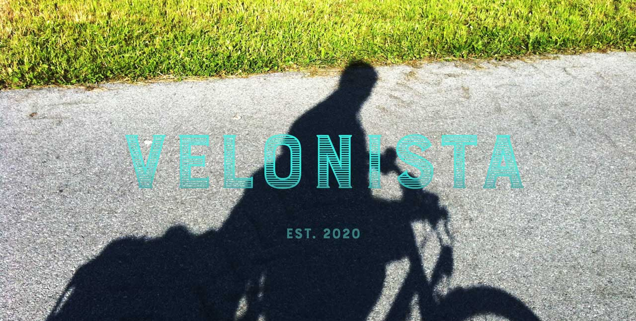 Schatten eines Fahrrads auf einem Weg von Wiese gesäumt